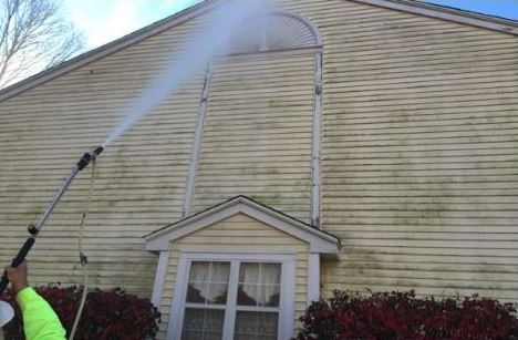 Pal's Power Washing in action on the exterior of a building with unattractive, harmful buildups